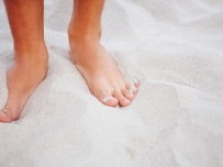 Feet on sandy beach